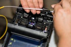 Кабель оптического волокна соединяя инженером с машиной профессионала аппаратуры Splicer сплавливания стекловолокна стоковые изображения