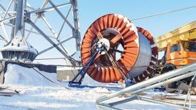 Кабель разматывает от огромной катушкы на башне среди снега акции видеоматериалы