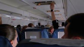 Кабина пассажира самолета с людьми в креслах во время полета видеоматериал