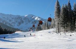 Кабины и лыжники кабел-крана на солнечный день на наклонах j стоковая фотография