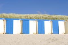 кабины пляжа голубые белые стоковая фотография