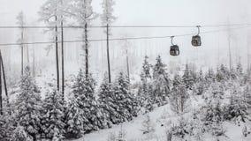 2 кабины подвесного подъемника проходя один другого на серый зимний день стоковая фотография rf