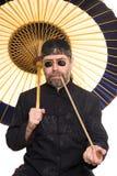 Кавказец в китайском costume курит трубу Стоковые Изображения