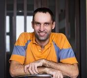 Кавказец сидя дома и усмехаясь Стоковые Фотографии RF