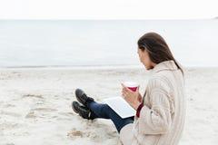 Кавказская дама сидя outdoors на пляже используя планшет Стоковые Фото