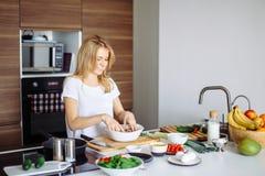 Кавказская белокурая женщина варя маринад для вкусных kebabs на кухонном столе стоковое изображение rf