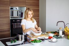 Кавказская белокурая женщина варя маринад для вкусных kebabs на кухонном столе стоковые изображения rf