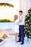 Кавказская белокурая женщина обнимая супруга около рождественской елки стоковые фотографии rf