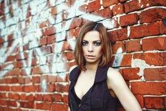 Кавказская белокурая женщина стоя за кирпичной стеной Стоковое Изображение RF