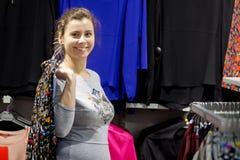 Кавказская девушка брюнет на покупках счастливая девушка приняла новое платье на вешалке в модном бутике Стоковые Изображения