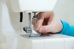 Кавказская девушка вводит поток в иглу швейной машины стоковая фотография