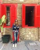 Кавказская девушка в солнечных очках Девушка с длинными волосами в костюме и белых тапках джинсовой ткани девушка стоит около ста Стоковое Фото