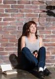 Кавказская девушка сидя на поле читая ужас или страшную книгу триллера Драматическое освещение с глазами девушек широко раскрывае Стоковое Изображение RF