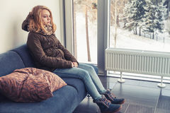Кавказская девушка в теплых одеждах сидя на голубой софе Стоковые Изображения RF
