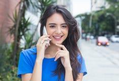 Кавказская девушка с голубой рубашкой смеясь над на телефоне в городе Стоковые Изображения
