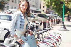 Кавказская женщина брюнет в непринужденном стиле сидя на велосипеде стоковые фото