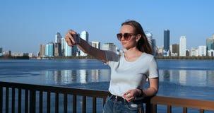 Кавказская женщина принимает selfies мобильным телефоном, outdoors в Марине Дубай в солнечном дне акции видеоматериалы