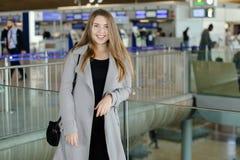 Кавказская женщина стоя на авиапорте, нося пальто Стоковые Фотографии RF