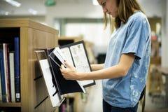 Кавказская книга чтения девушки в библиотеке Стоковое Фото