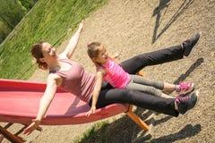 Кавказская мать и дочь играя на скольжении в спортивной площадке Стоковые Фотографии RF