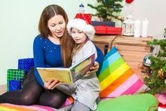 Кавказская мать читая дочь книги около зеленого дерева на ноче перед рождеством Стоковое Изображение RF