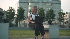 Кавказская молодая бизнес-леди в белых рубашке и стеклах сидит на стенде в улице и работает за ноутбуком акции видеоматериалы