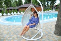 Кавказская молодая женщина сидя в привесном белом стуле, бассейн в предпосылке стоковые фото