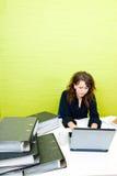 Кавказская молодая женщина работая на ее портативном компьютере на ее столе Стоковые Фотографии RF