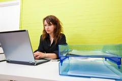 Кавказская молодая женщина работая на ее портативном компьютере на ее столе Стоковые Изображения