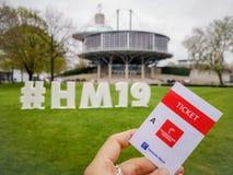 Кавказская рука держа бумажный входной билет к Ганновер Messe внутри ярмарочных площадей стоковая фотография rf