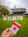 Кавказская рука держа бумажный входной билет к Ганновер Messe внутри ярмарочных площадей стоковая фотография