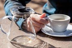 Кавказская рука женщины держит керамическую чашку с черным чаем и молоком, пустым стеклянным чайником рядом с ей Стоковые Изображения