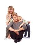 Кавказская счастливая усмехаясь молодая семья при 2 дет сидя o Стоковые Изображения RF