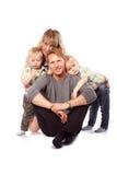 Кавказская счастливая усмехаясь молодая семья при 2 дет сидя o Стоковые Фотографии RF