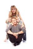 Кавказская счастливая усмехаясь молодая семья при 2 дет сидя o Стоковая Фотография RF