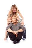 Кавказская счастливая усмехаясь молодая семья при 2 дет сидя o Стоковая Фотография