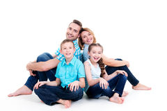 Кавказская счастливая усмехаясь молодая семья с 2 детьми