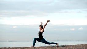 Кавказская тонкая милая йога женщины на пляже акции видеоматериалы