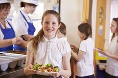 Кавказская школьница держит плиту еды в школьном кафетерии стоковое изображение rf