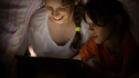 Кавказские девушки играя таблетку игр под одеялом на ноче видеоматериал