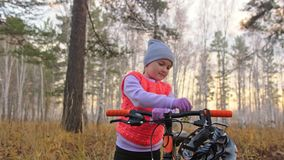 Кавказские дети одно идут с велосипедом в парке осени Маленькая девочка идя черный оранжевый цикл в ребенк леса идет сделать акции видеоматериалы