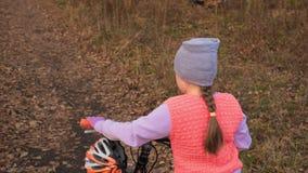 Кавказские дети одно идут с велосипедом в парке осени Маленькая девочка идя черный оранжевый цикл в ребенк леса идет сделать сток-видео