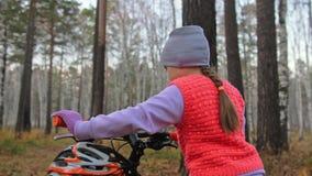 Кавказские дети одно идут с велосипедом в парке осени Маленькая девочка идя черный оранжевый цикл в ребенк леса идет сделать видеоматериал