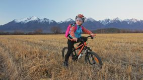 Кавказские дети одно идут с велосипедом в пшеничном поле Девушка идя черный оранжевый цикл на предпосылке красивое снежного акции видеоматериалы