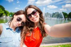 Кавказские девушки делая предпосылкой selfie большой фонтан Молодые туристские друзья путешествуя на праздниках outdoors усмехаяс Стоковое Изображение RF