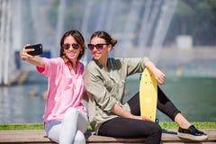 Кавказские девушки делая предпосылкой selfie большой фонтан Молодые туристские друзья путешествуя на праздниках outdoors усмехаяс Стоковые Фотографии RF