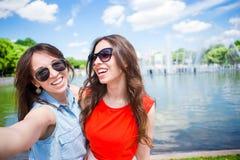 Кавказские девушки делая предпосылкой selfie большой фонтан Молодые туристские друзья путешествуя на праздниках outdoors усмехаяс Стоковые Фото