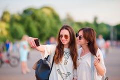 Кавказские девушки делая selfie outdoors Молодые туристские друзья путешествуя на усмехаться праздников счастливый Стоковые Фото
