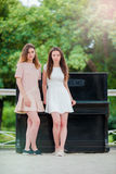 Кавказские девушки наслаждаются выходными лета в рояле парка внешнем близко большом Молодые туристские друзья на праздниках outdo Стоковое Фото