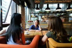 Кавказские женщины сидя на уютном кофе кафа, усмехаться и выпивать Стоковое фото RF